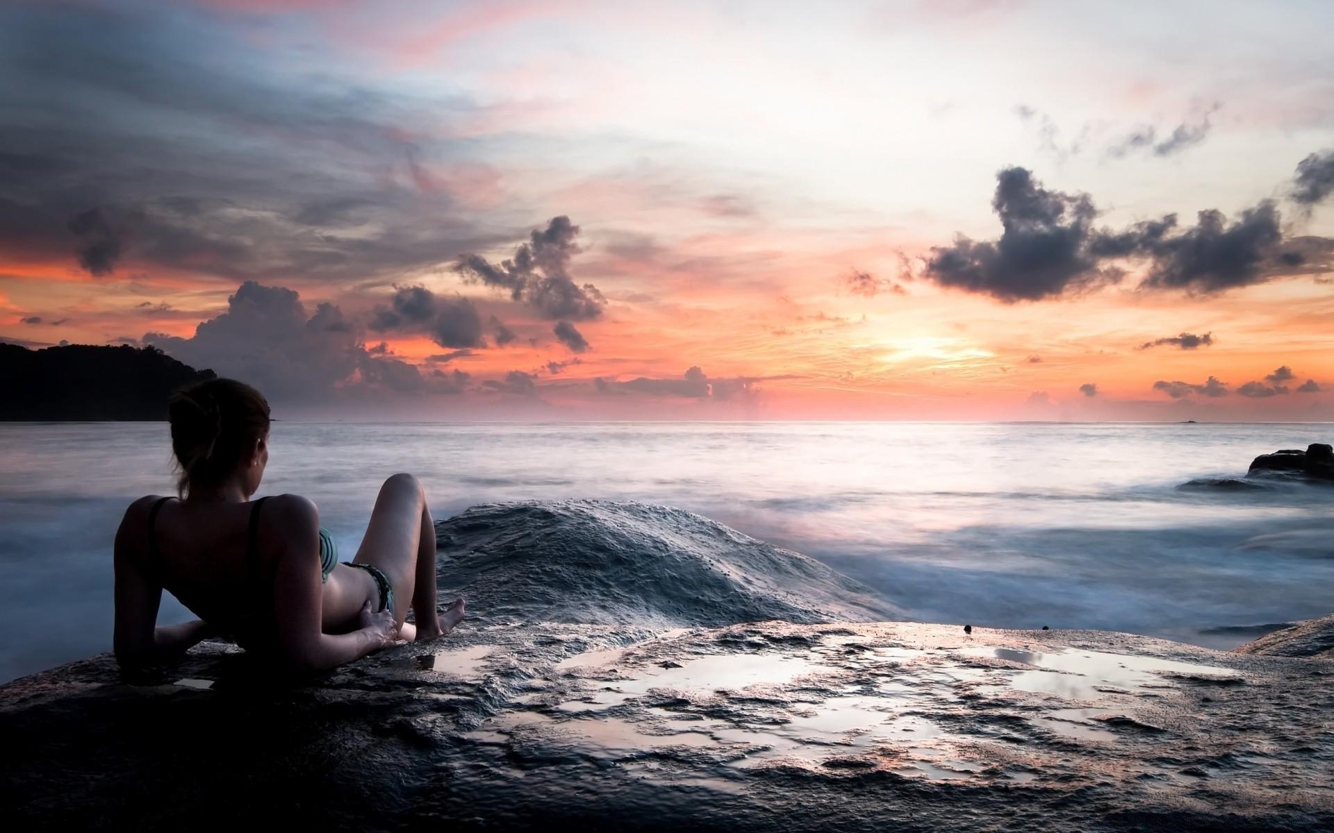 Красивая девушка на фоне красивого пейзажа залезла под стул